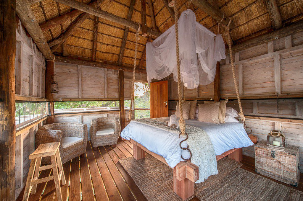 full view of the treehouse room at pondoro treehouse with bed and sitting room as the focus