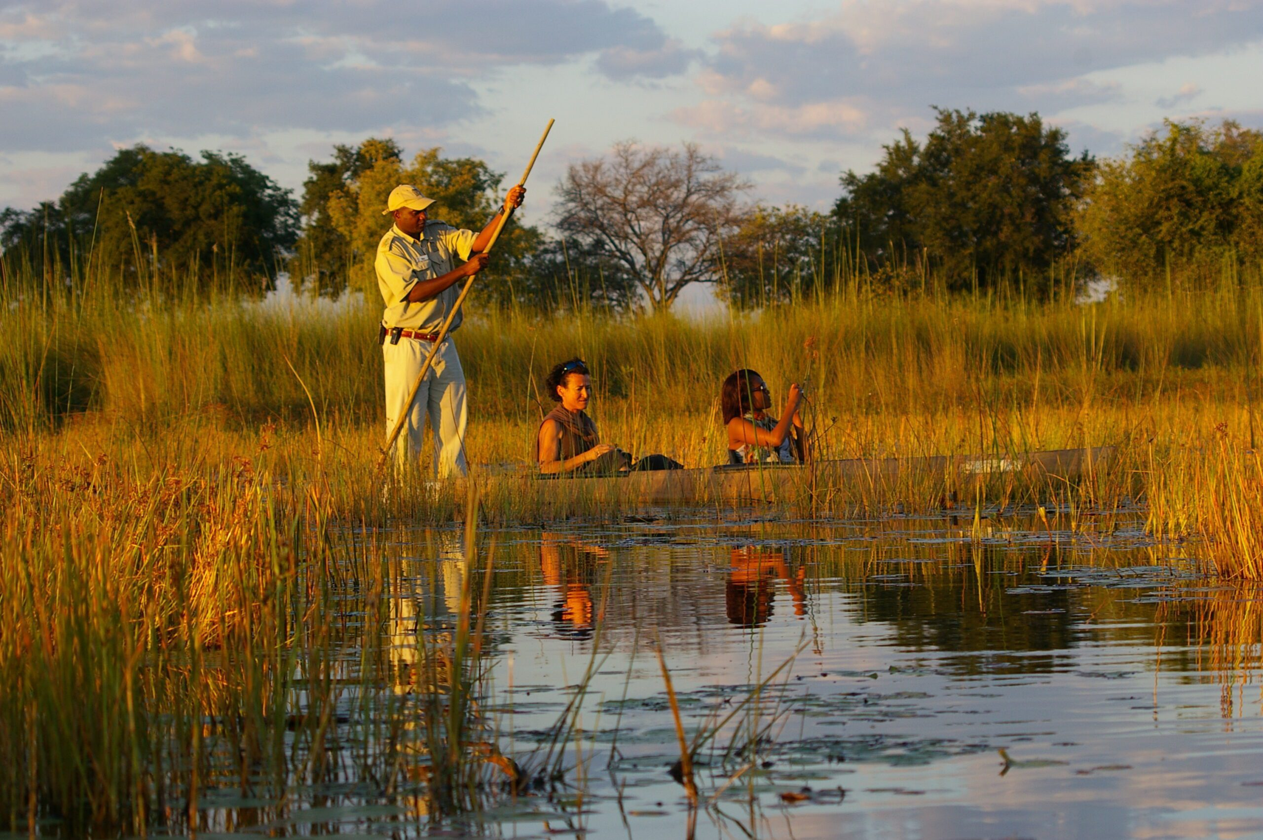 mokoro in the waterways of okavango delta at xugana camp with 2 people and 1 guide