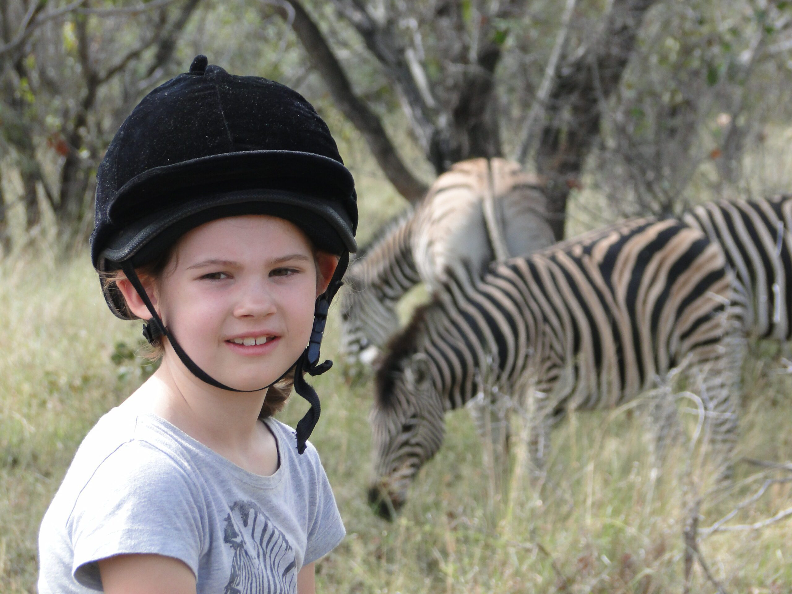 a young girl in a t-shirt wearing a riding helmet stops to pose for a photo in front of two zebra in the bush safari on horseback