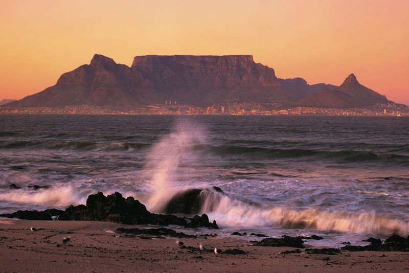 ocean spray against the rocks looking across the ocean to Table Mountain, Cape Town