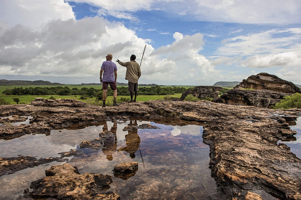 Guide from Bamurru Plains in the Top End with a guest looking over a vast landscape of rocks and forest on a northern Australia holiday