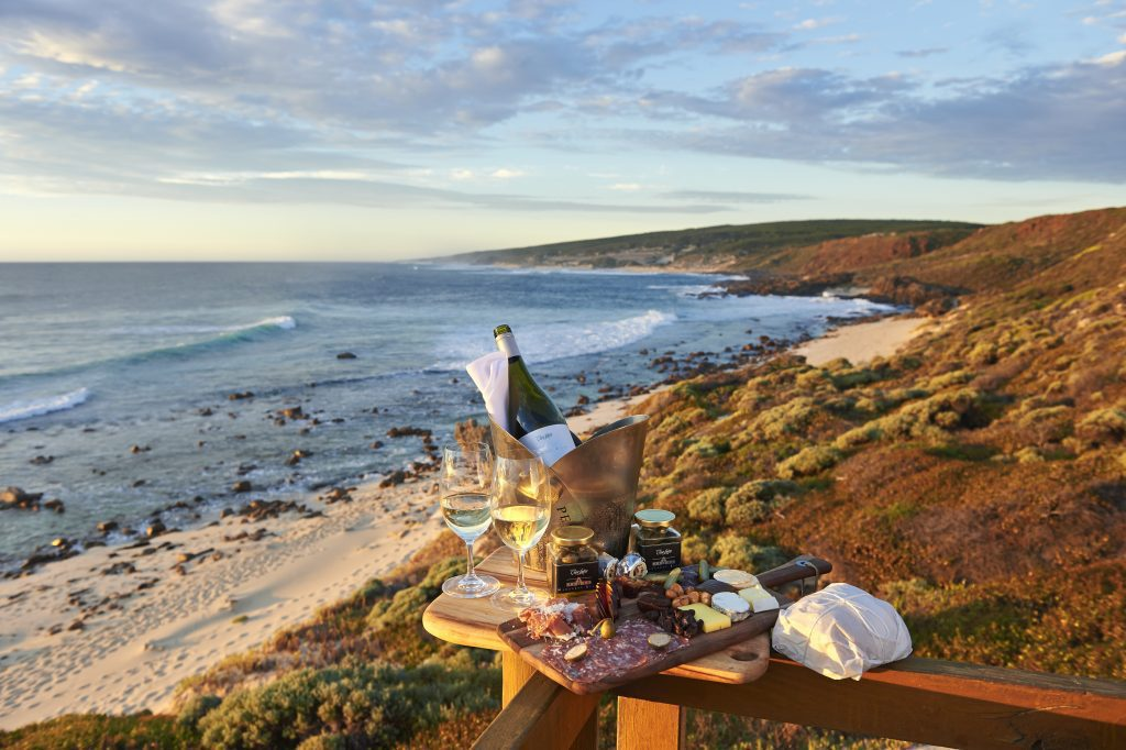 A decadent charcuterie board with wine rests on a railing above the ocean for a private sundowner in Margaret River