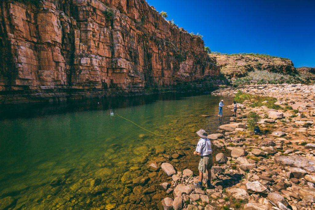 A couple people fish for Barramundi in a river at the base of a sheer cliff face in the Kimberley on a fishing safari