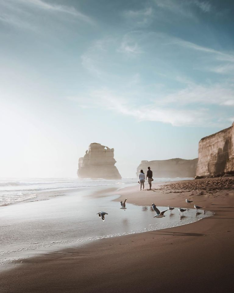 Couple walks along Gibsons Steps on the Great Ocean Road at the Twelve Apostles with mist coming off the ocean.