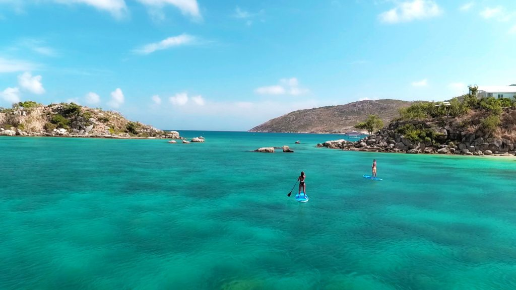 A couple stand up paddleboarding at Lizard Island