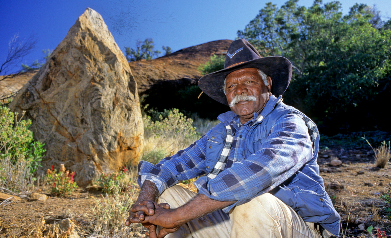 An Aboriginal guide from SEIT Outback tours rests on a rock in the red center