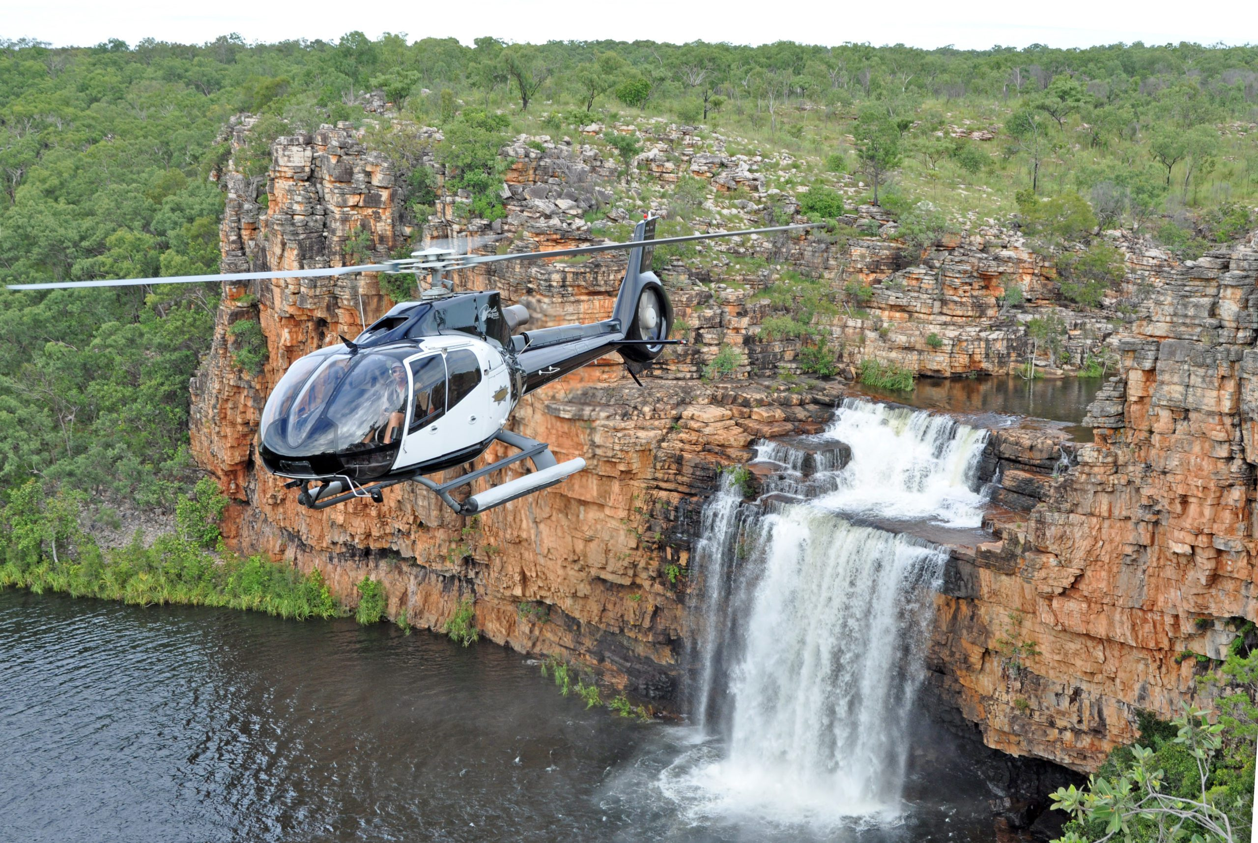 A helicopter flies above a waterfall in Kimberley