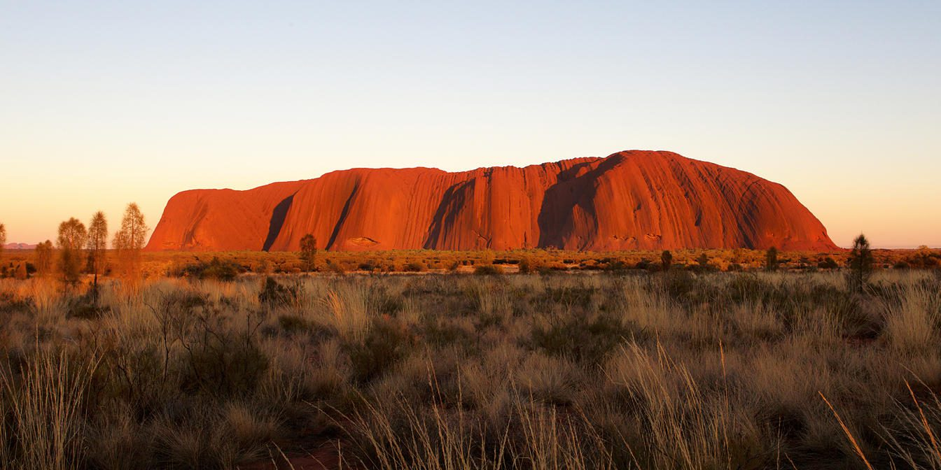 Uluru commands the landscape, bright red at sunset