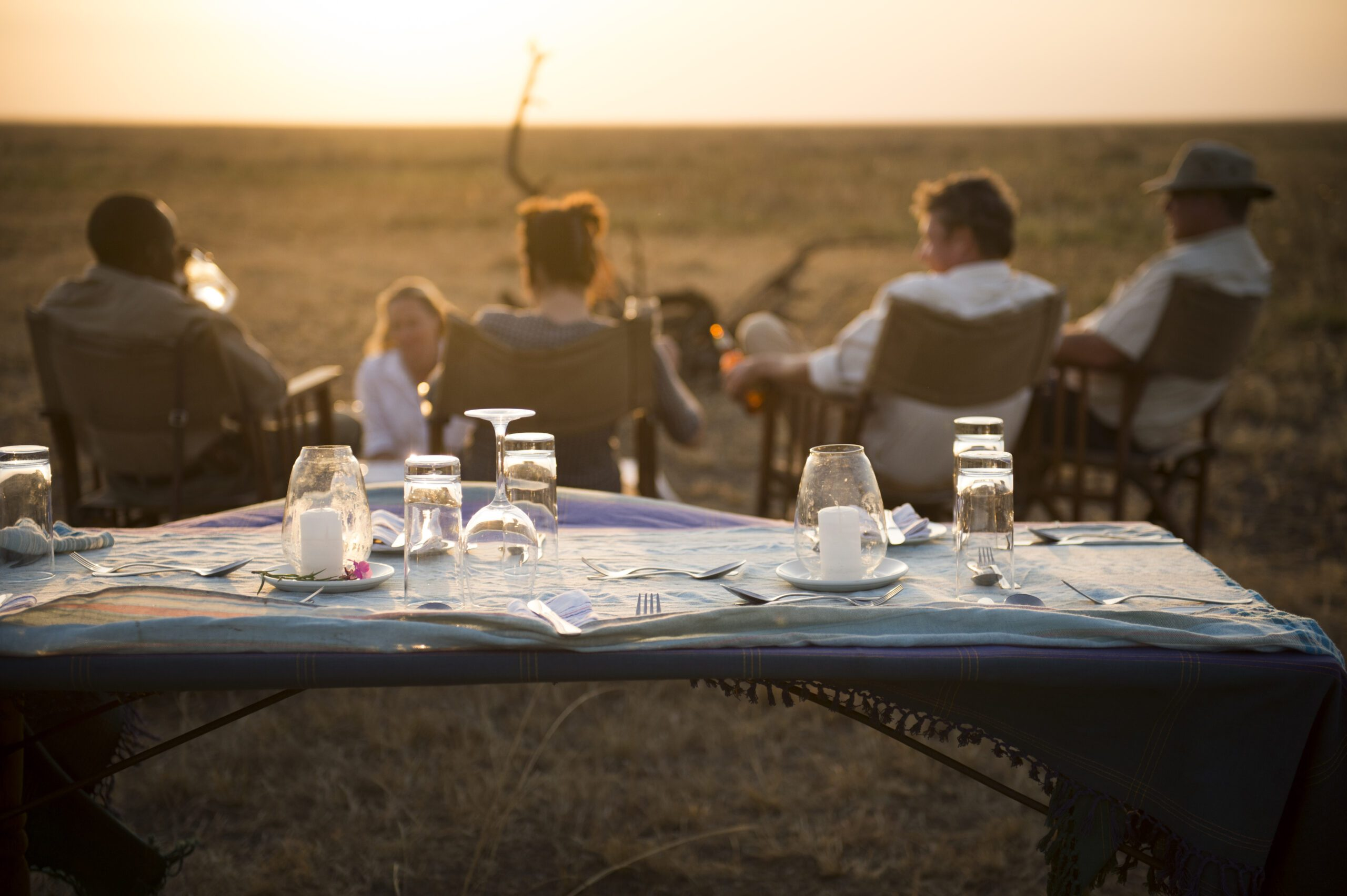 table set up outside with guests sitting in chairs looking out onto the open plains at sunset