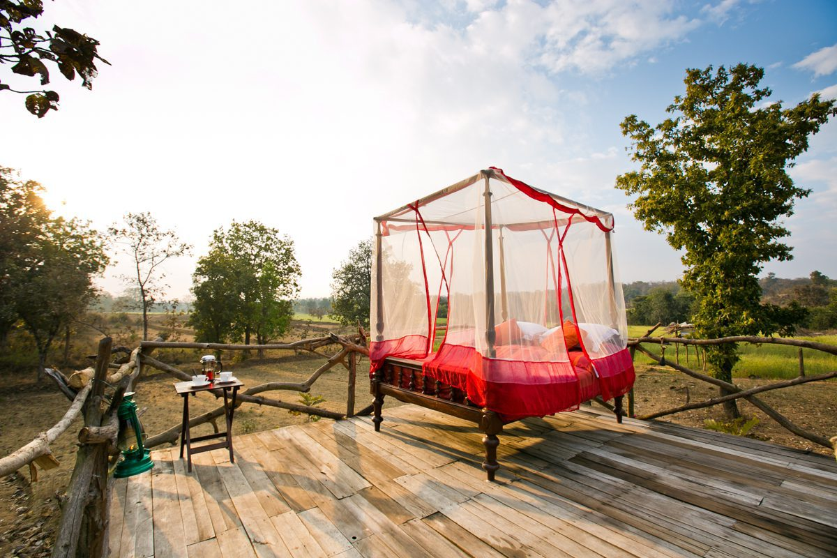 red mosquito net over red sheets of a star bed under a blue sky at Jamtara Wilderness