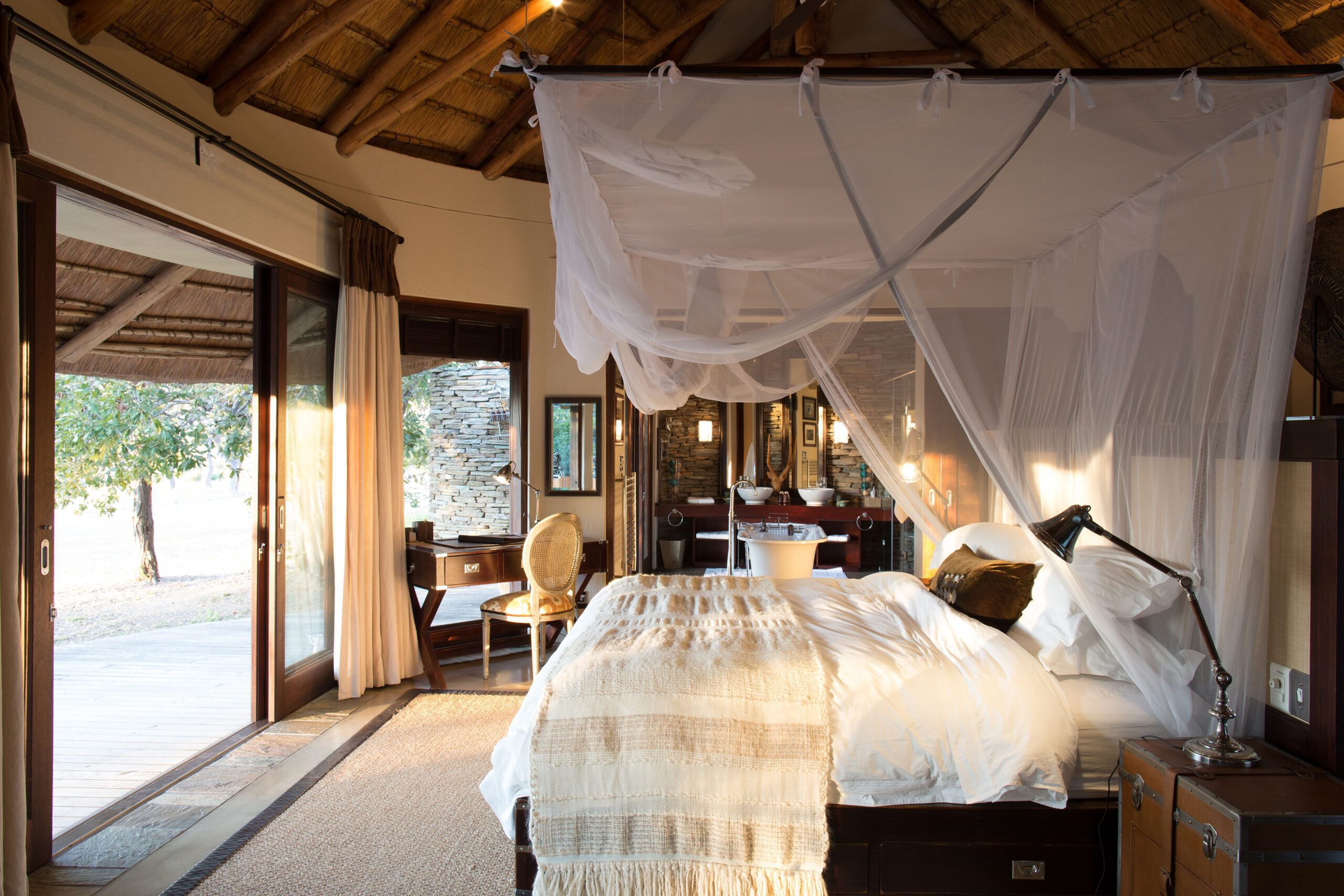 bed draped with mosquito net looking out to the bush at makanyi lodge on this South Africa and Namibia safari