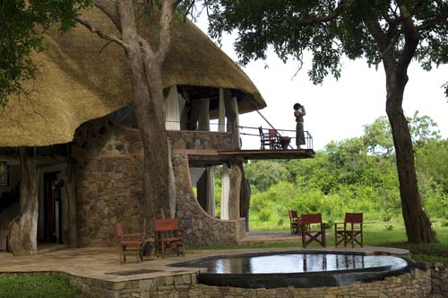 person looking through binoculars on the balcony of Luangwa House