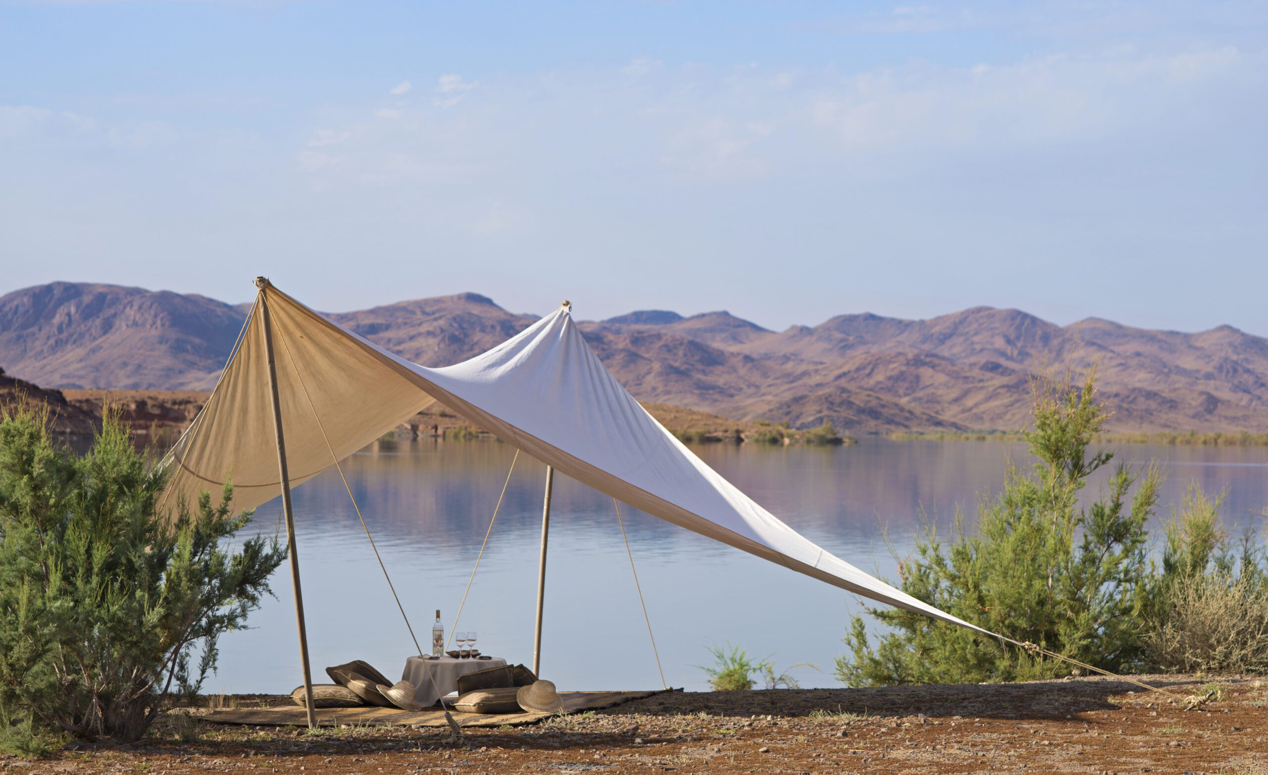 white cloth making a tent with bean bag chairs overlook a body of water and mountains at Dah Ahlam