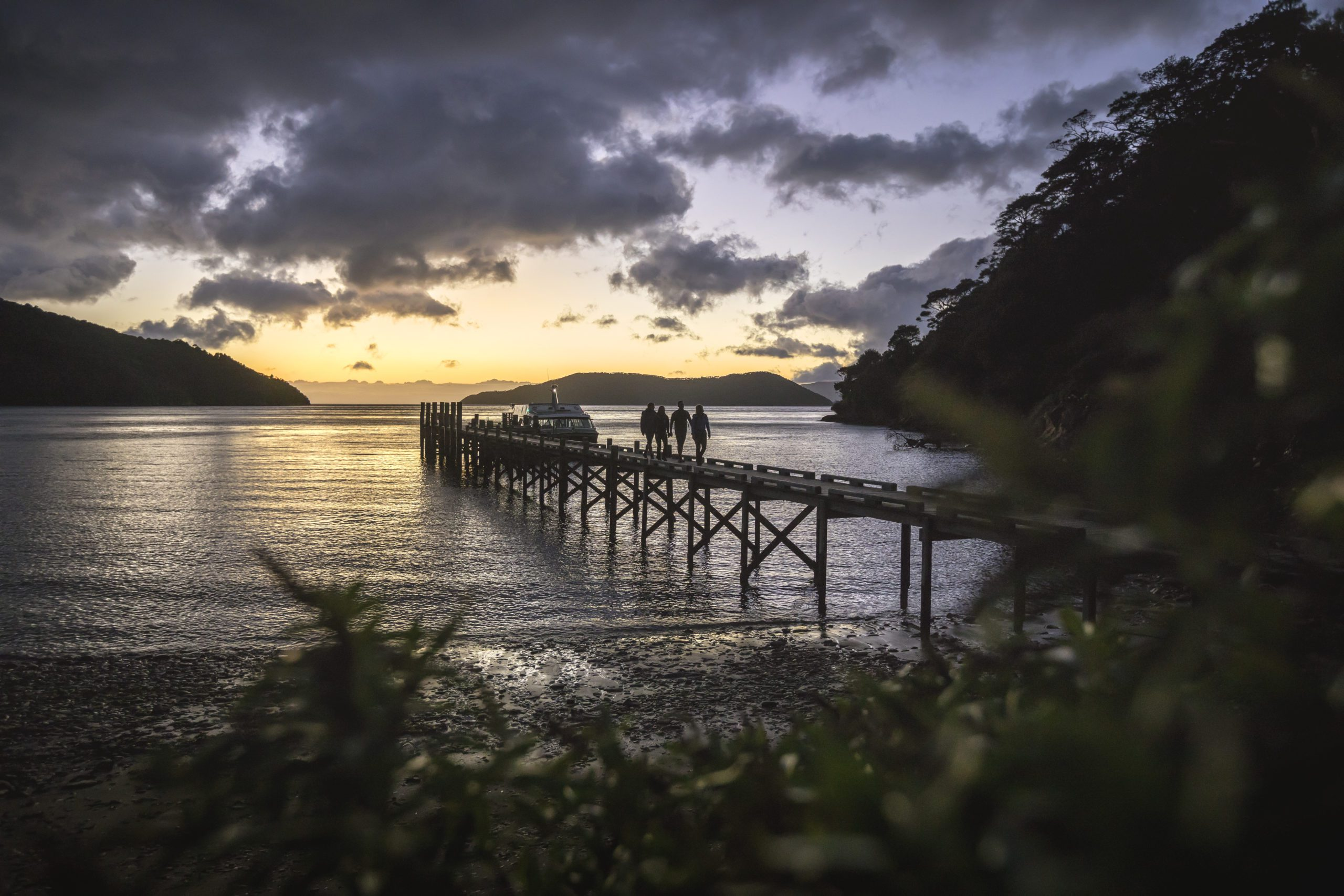 People walking along the jetty in Picton at sunset.