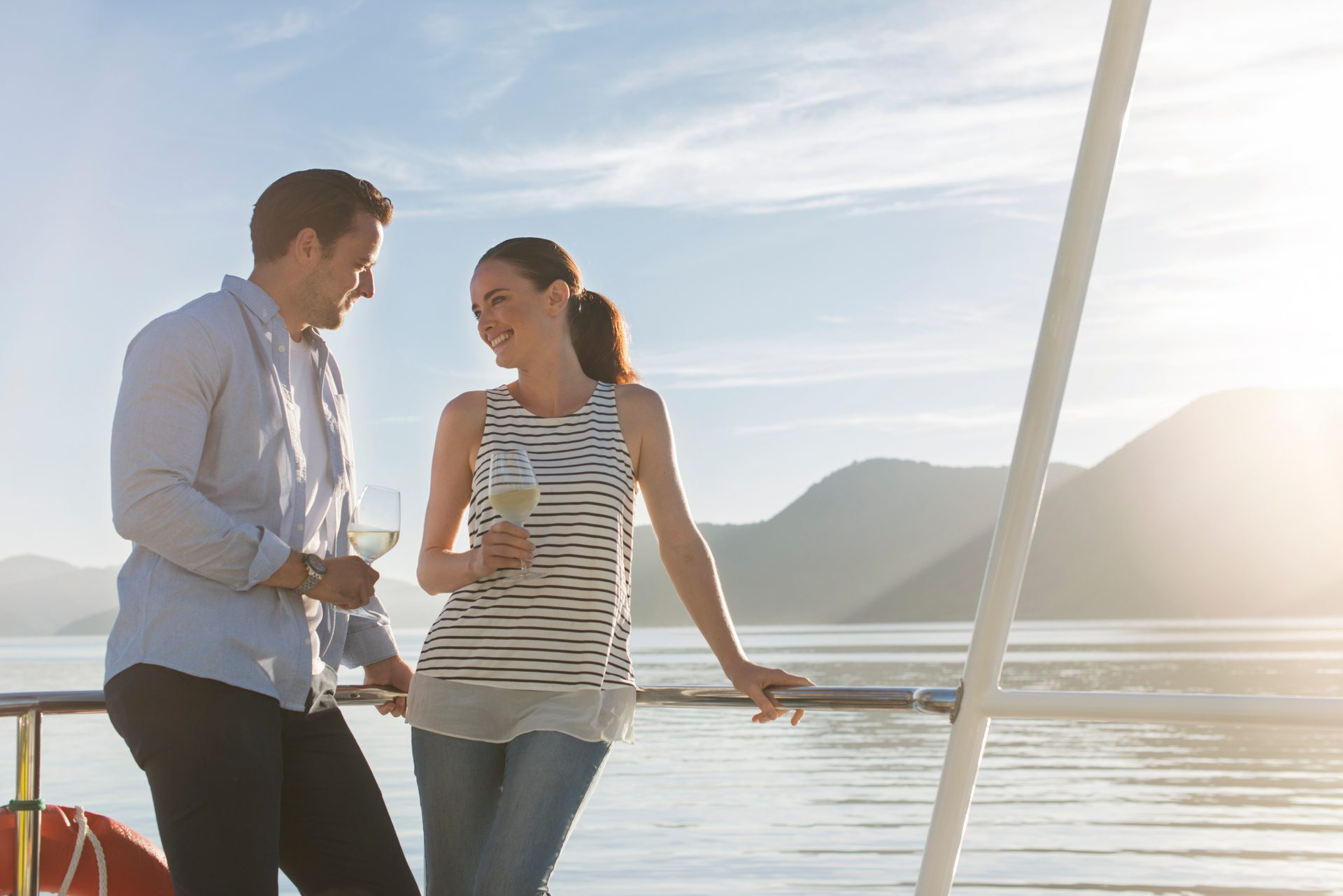 A couple enjoying a glass of wine on a yacht in the Queen Charlotte Sound.