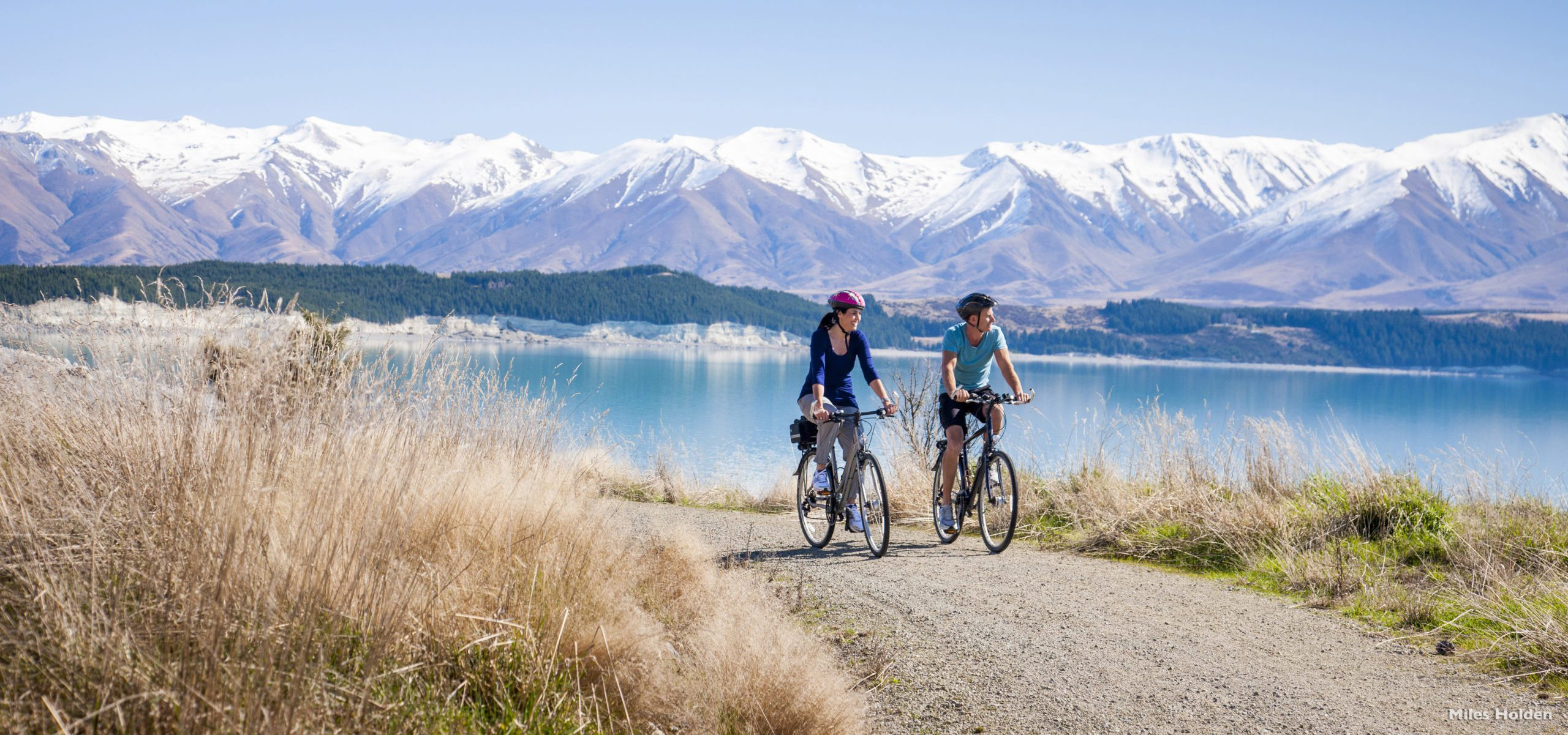Two cyclists biking along Lake Pukaki with the Southern Alps in the background on New Zealand's South Island tour