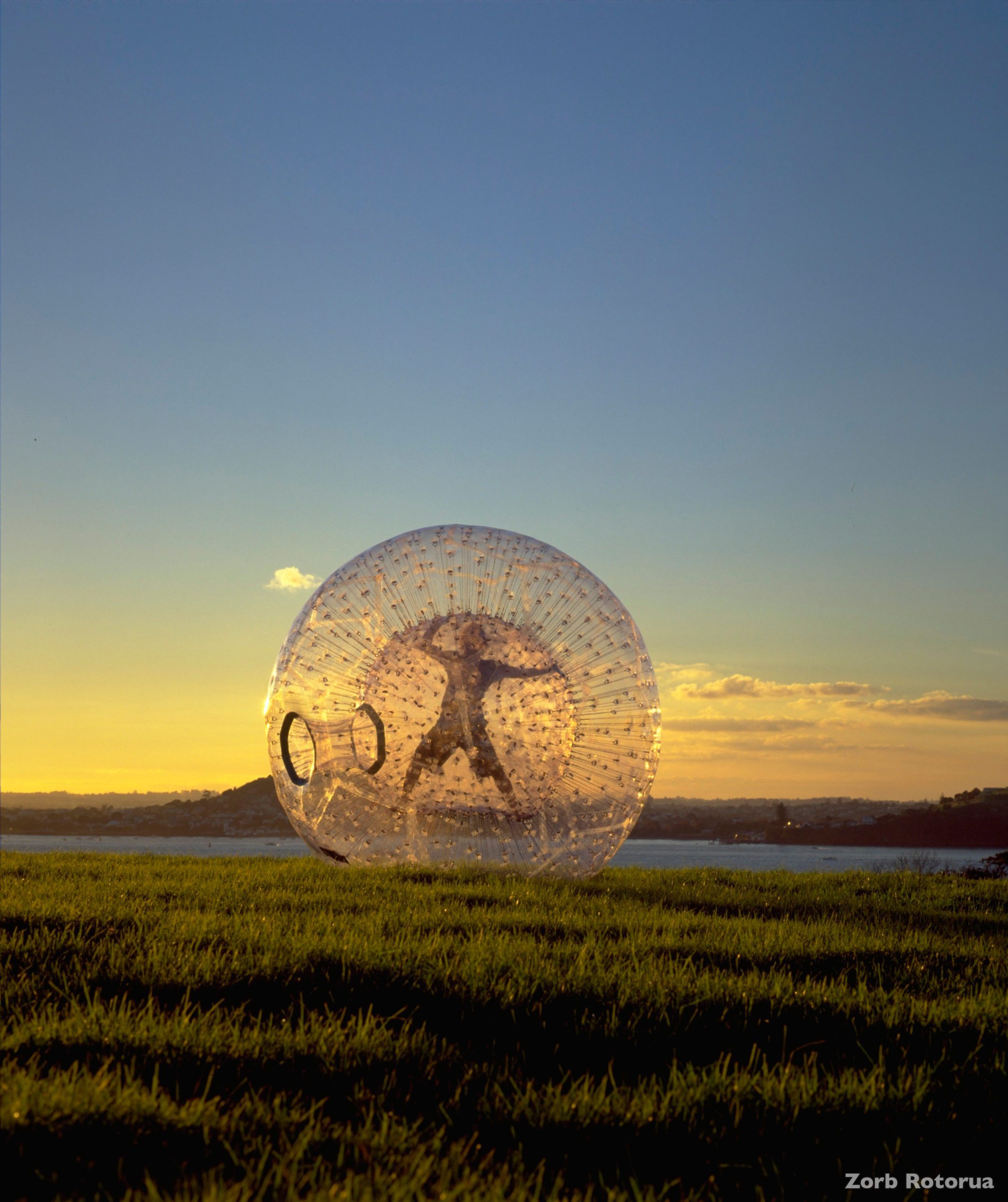 A person in a star-position Zorbing down a hill at dusk