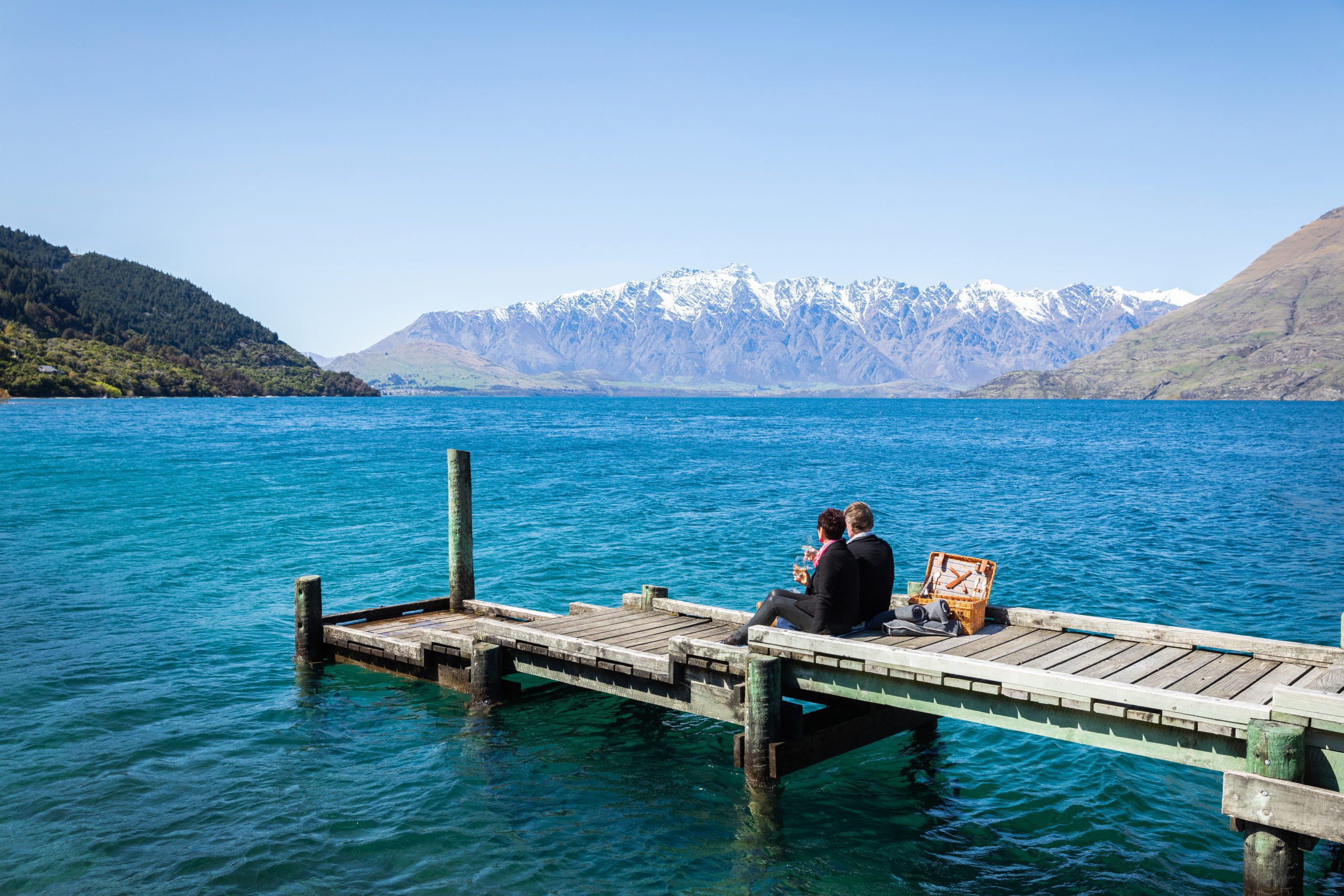 A couple enjoys a private picnic on the jetty at Matakauri Lodge, overlooking Lake Wakatipu and the Remarkables on safari in New Zealand