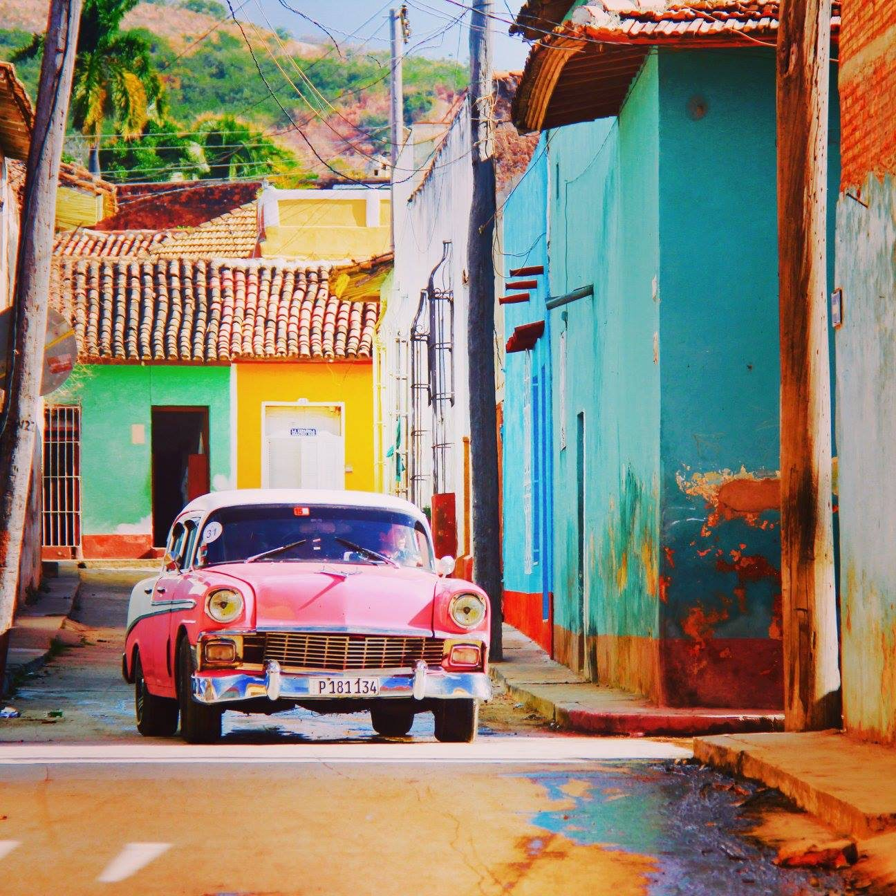 pink car driving through colorful street on a safari in the Americas