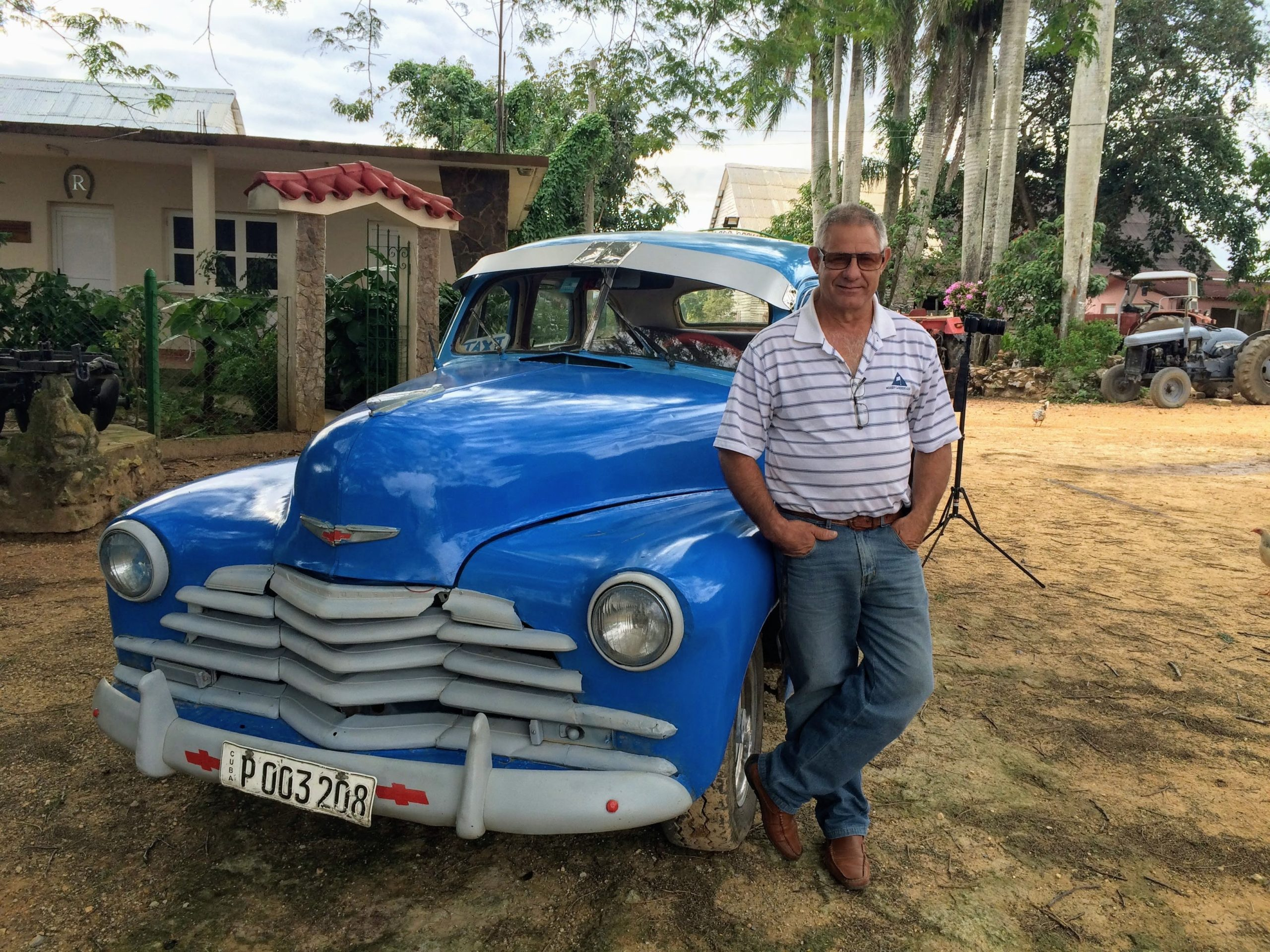 Driver Benino standing beside classic blue car in Vinales