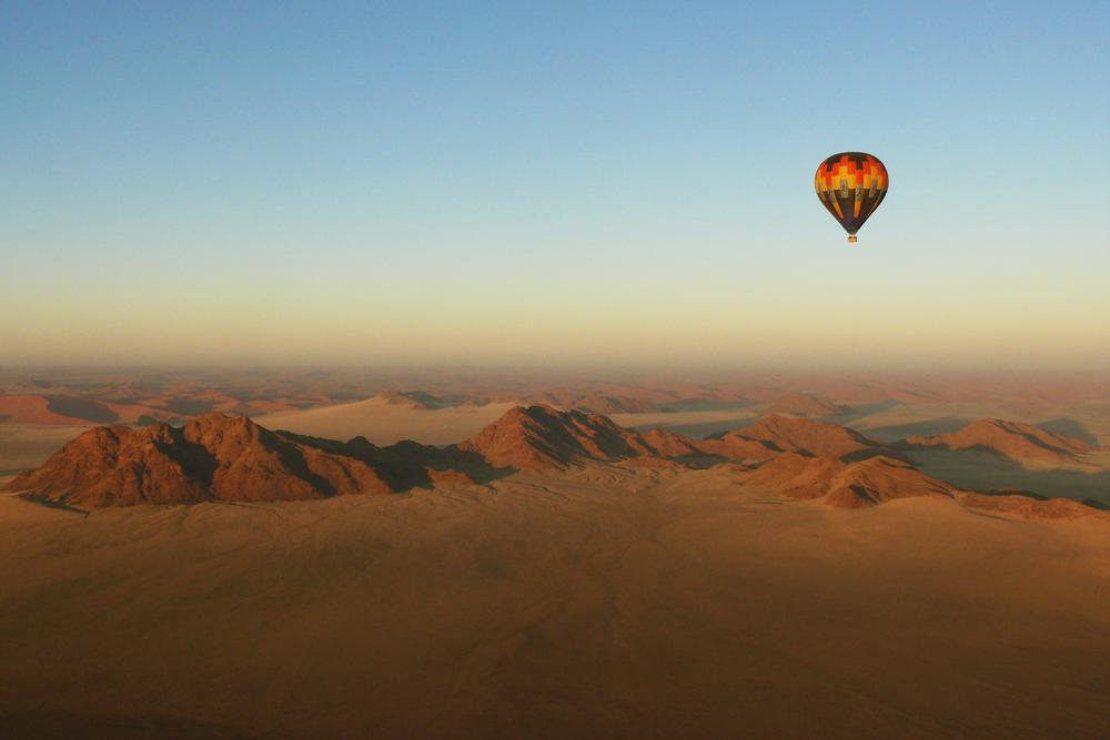 on your next Africa safari see the Sossusvlei desert with aerial view of hot air balloon and mountains