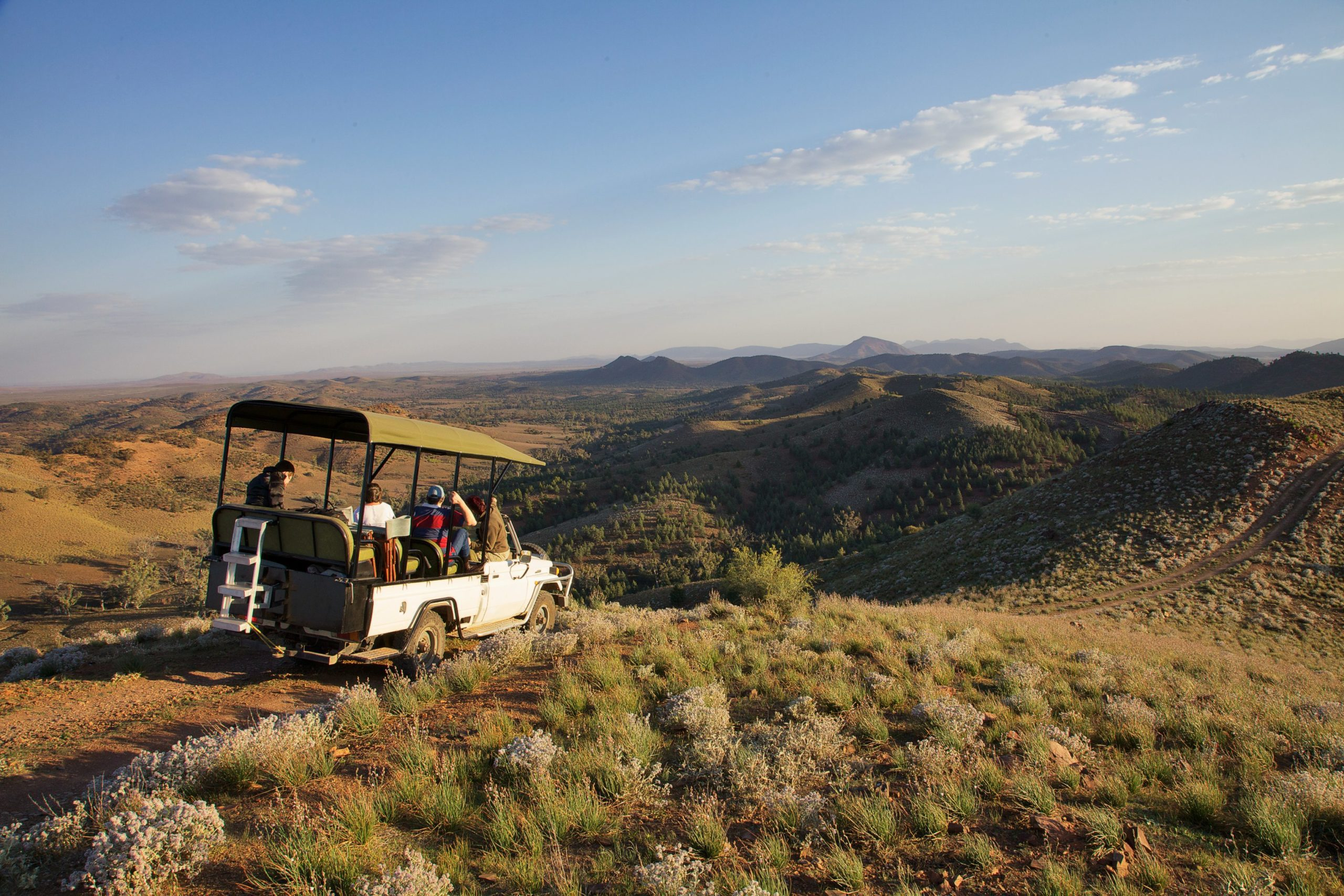 A safari vehicle driving on a dirt road through the hills of the Flinders Ranges at Arkaba