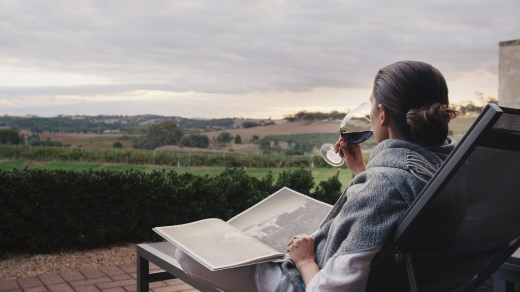 Woman enjoy a glass of red wine while reading a book and enjoying relaxing views over the vineyards at The Louise on our trips of a lifetime