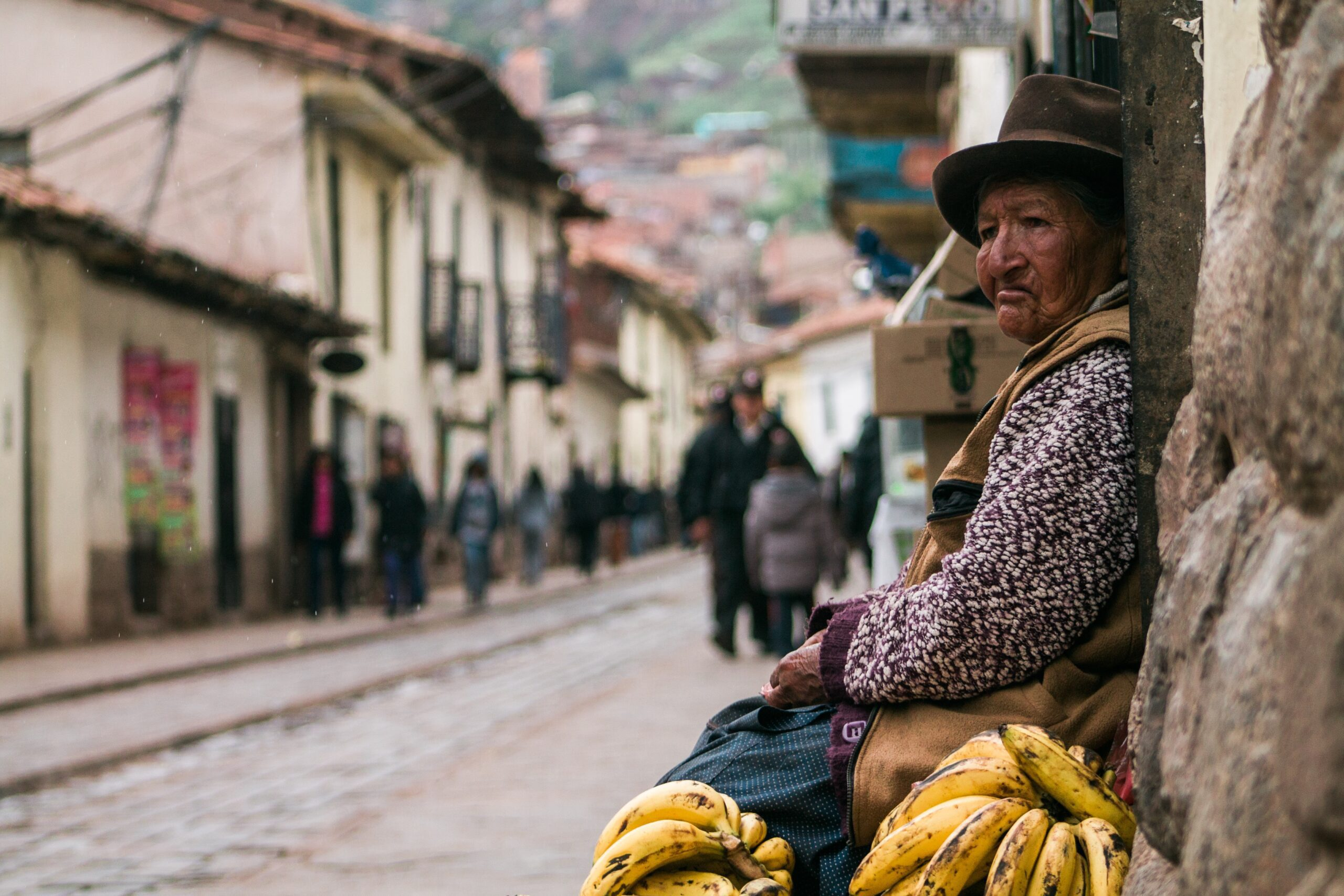 Peruvian woman sitting on side of street in cusco with bananas