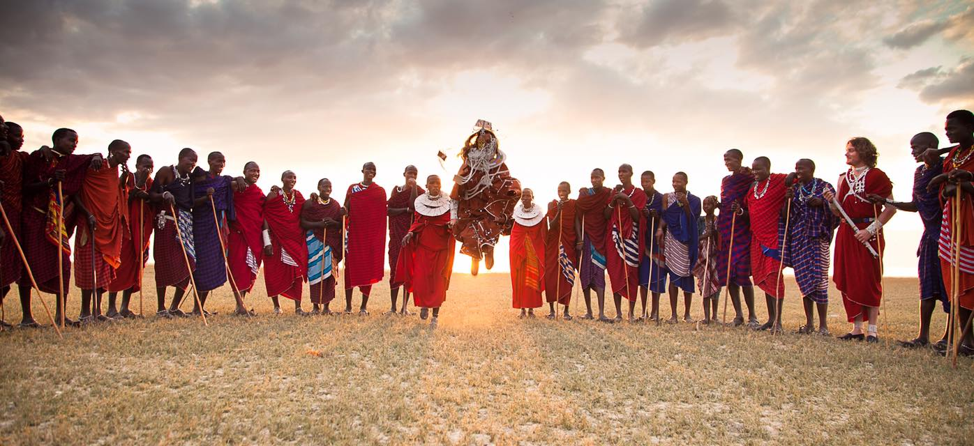group of local villagers in Tanzania dressed in traditional red robes on this luxury Tanzania safari