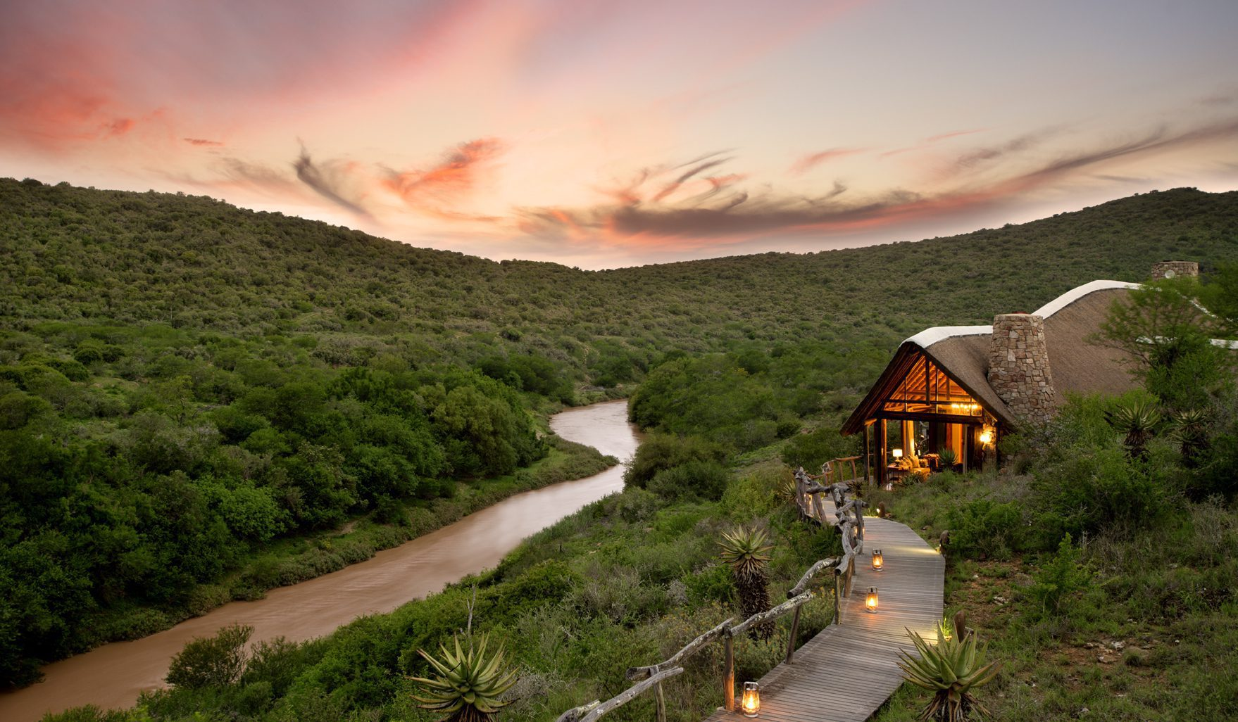 beautiful dusk view of the orange sky over the calm river at kwandwes great fish river lodge