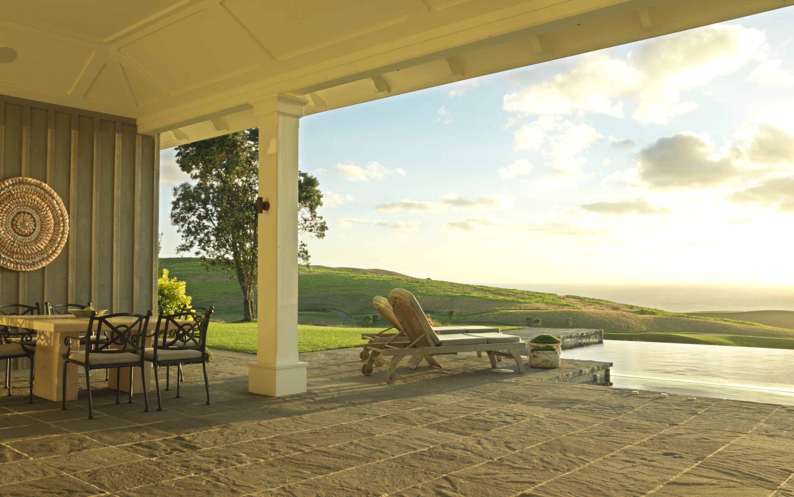 View from the deck of a room at Kauri Cliffs overlooking green hills.