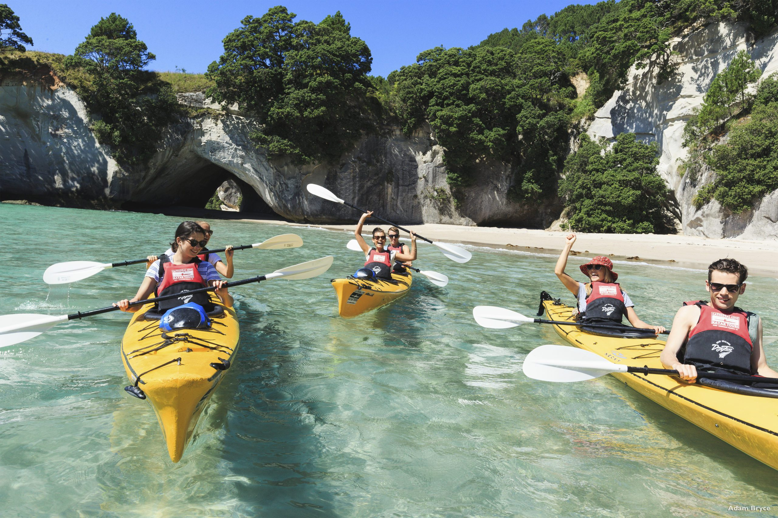 A group kayaking in the clear waters below some cliff faces in Coromandel.
