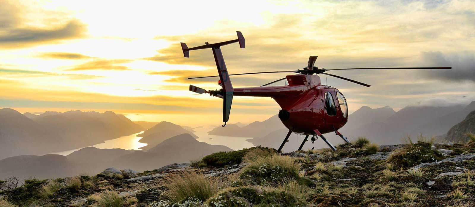 A helicopter lands on a peak in Fiordland overlooking the fiords from Fiordland Lodge.
