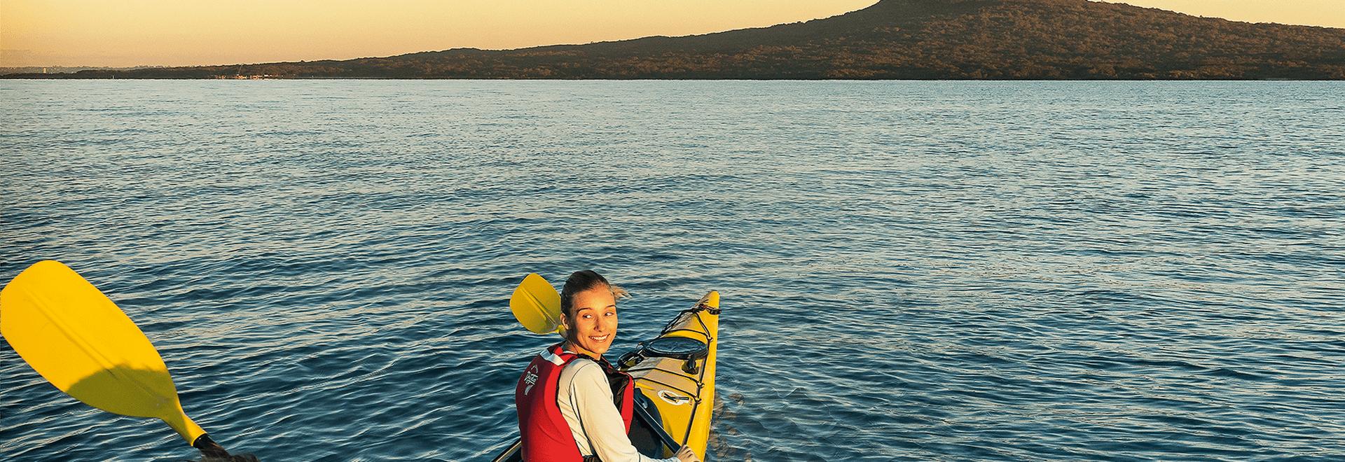 A happy young lady kayaks toward Rangitoto Island at dusk.
