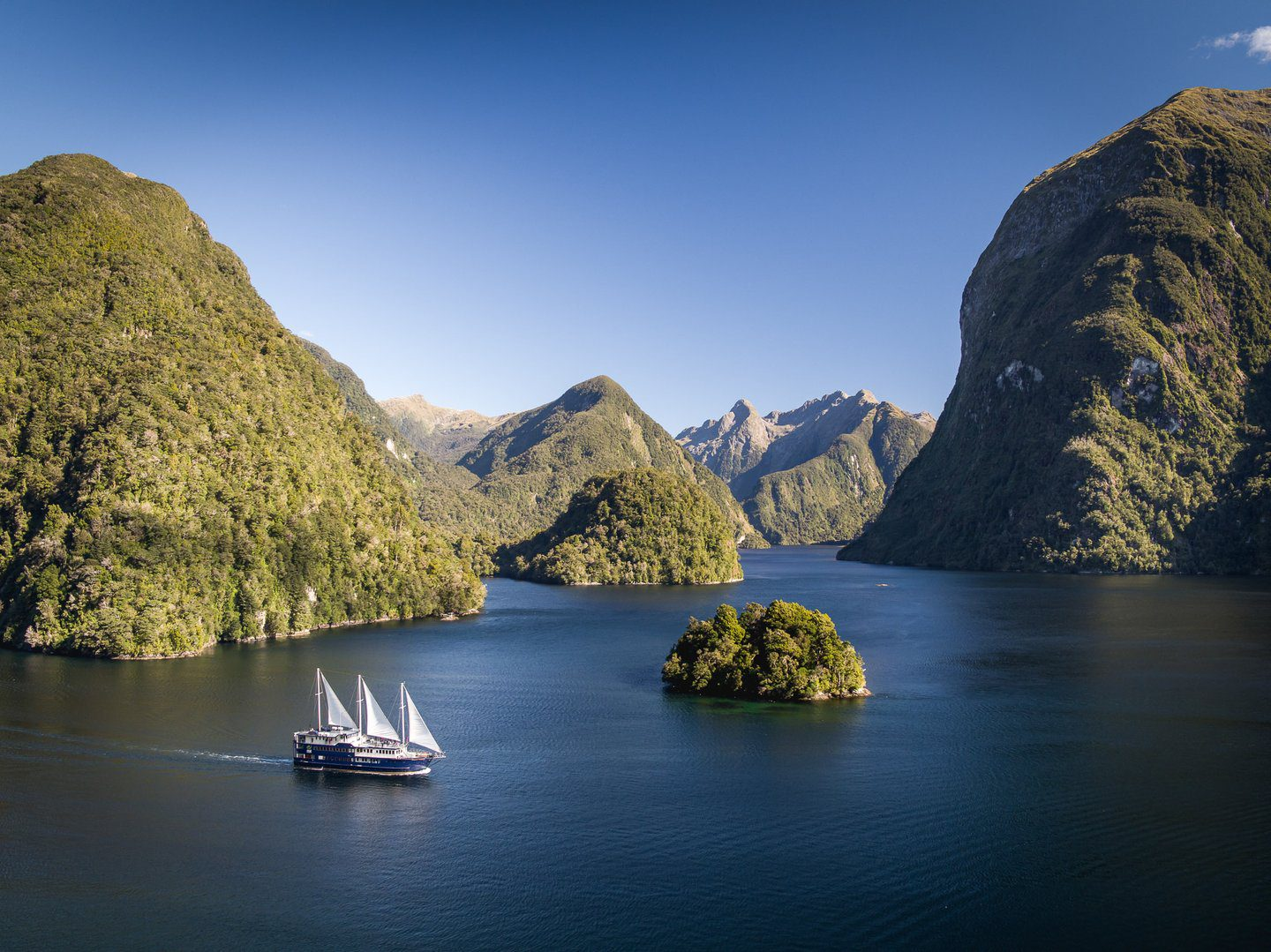 Real Journeys ship cruising with it's sails out through the Doubtful Sound on an Oceania safari