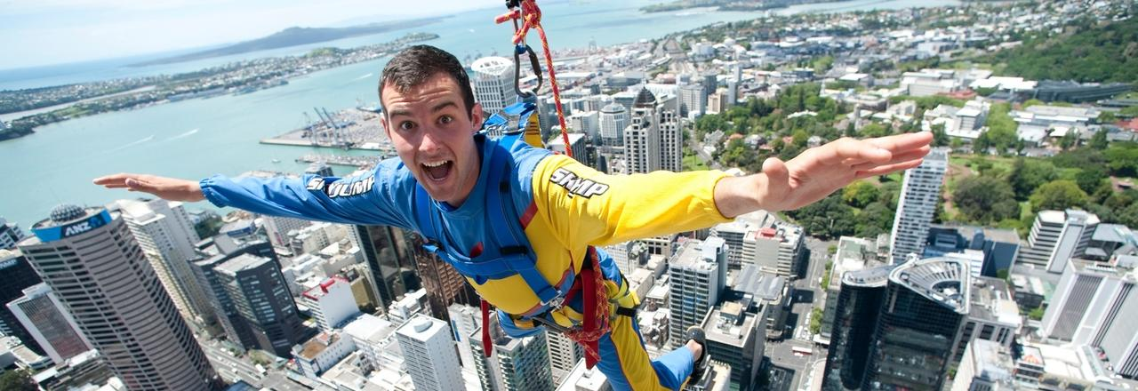 A happy young many doing the SkyJump in Auckland with the city and harbors in the background.