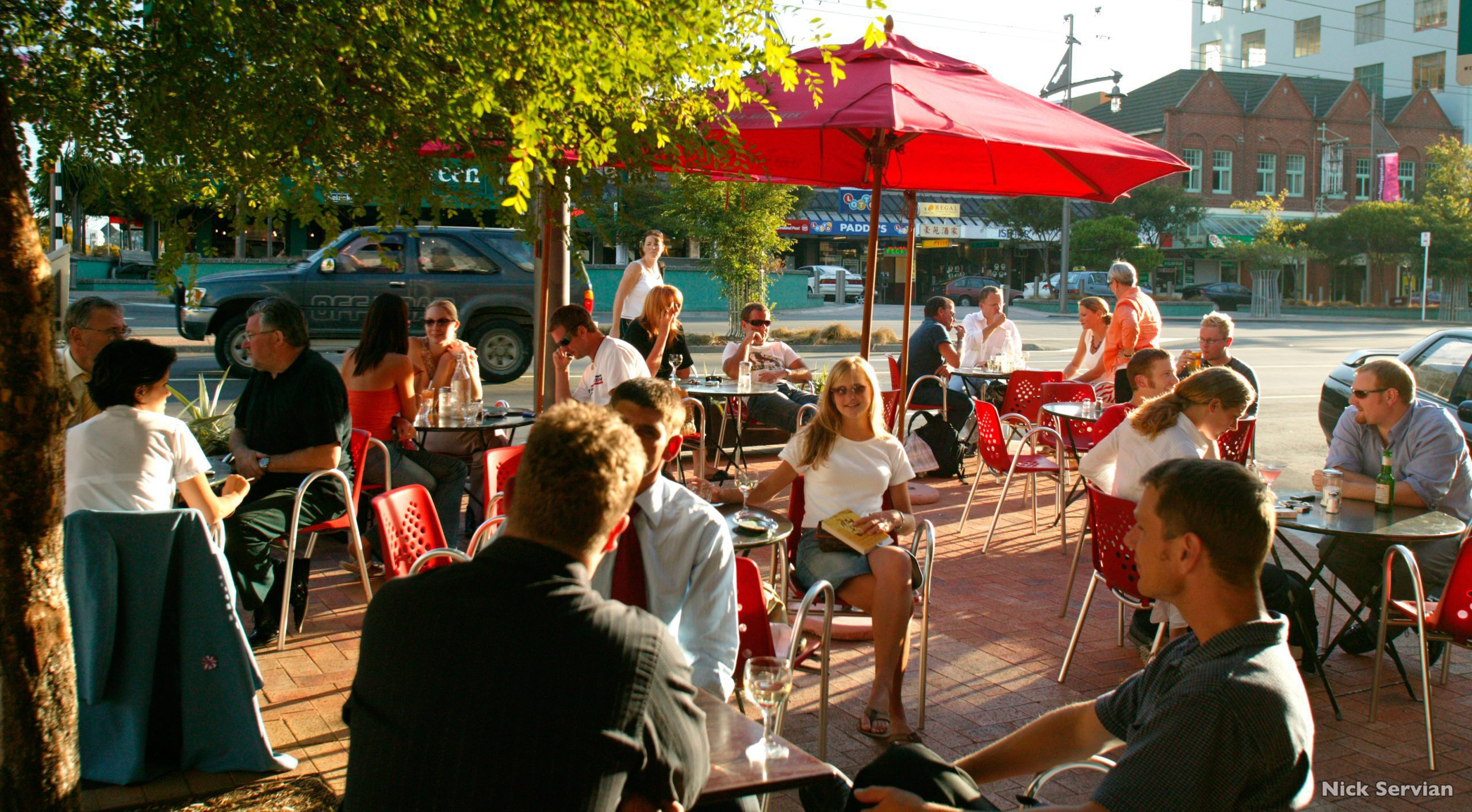 people eating and drink outside beneath umbrellas at a cafe in Wellington