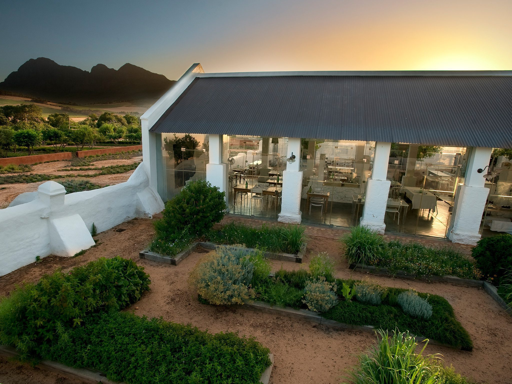pretty orange and yellow sunset as the backdrop of the main exterior dining room at babel in the winelands