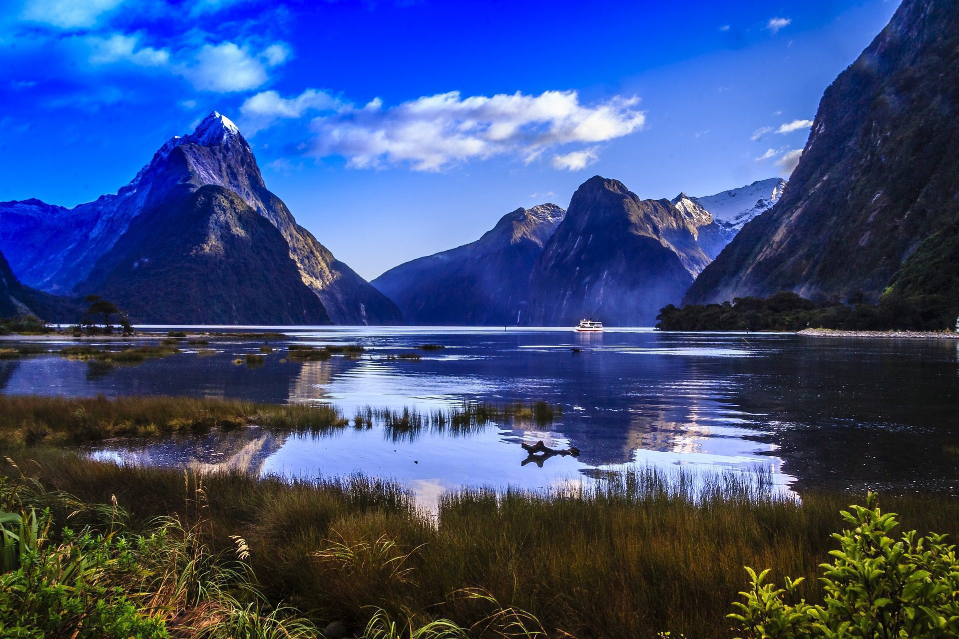 dramatic fjord scenery in Fiordland on a clear day with reflecting peaks in the sound on New Zealand tour