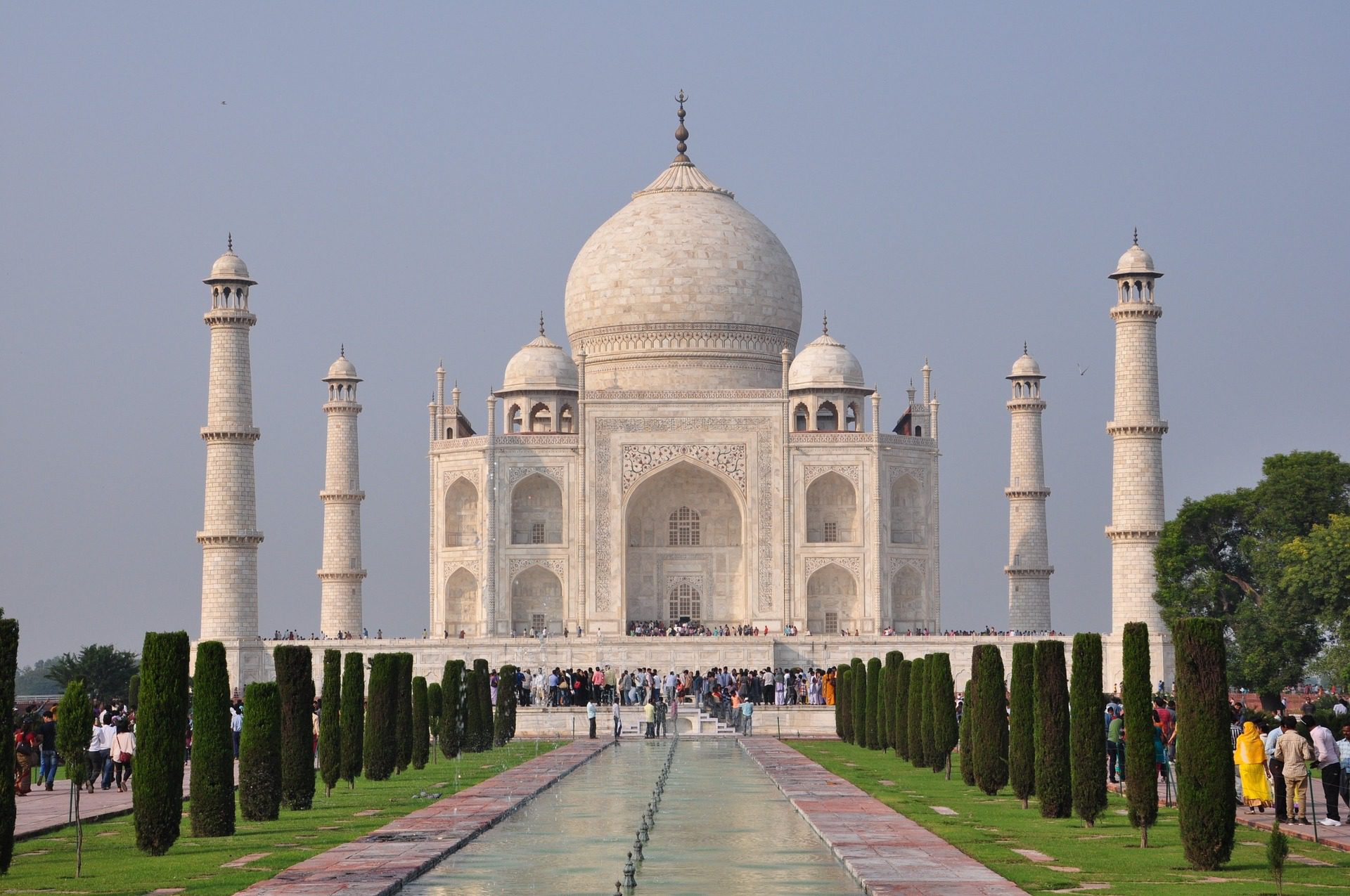 The Taj Mahal displaying perfect symmetry with landscaping and a reflecting pool in the foreground on India holiday