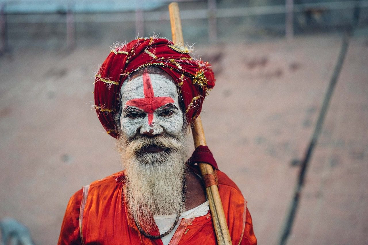 Holy man with a long white beard whose face is painted white with a red cross across his forehead and bright red clothing and turban in Varanasi