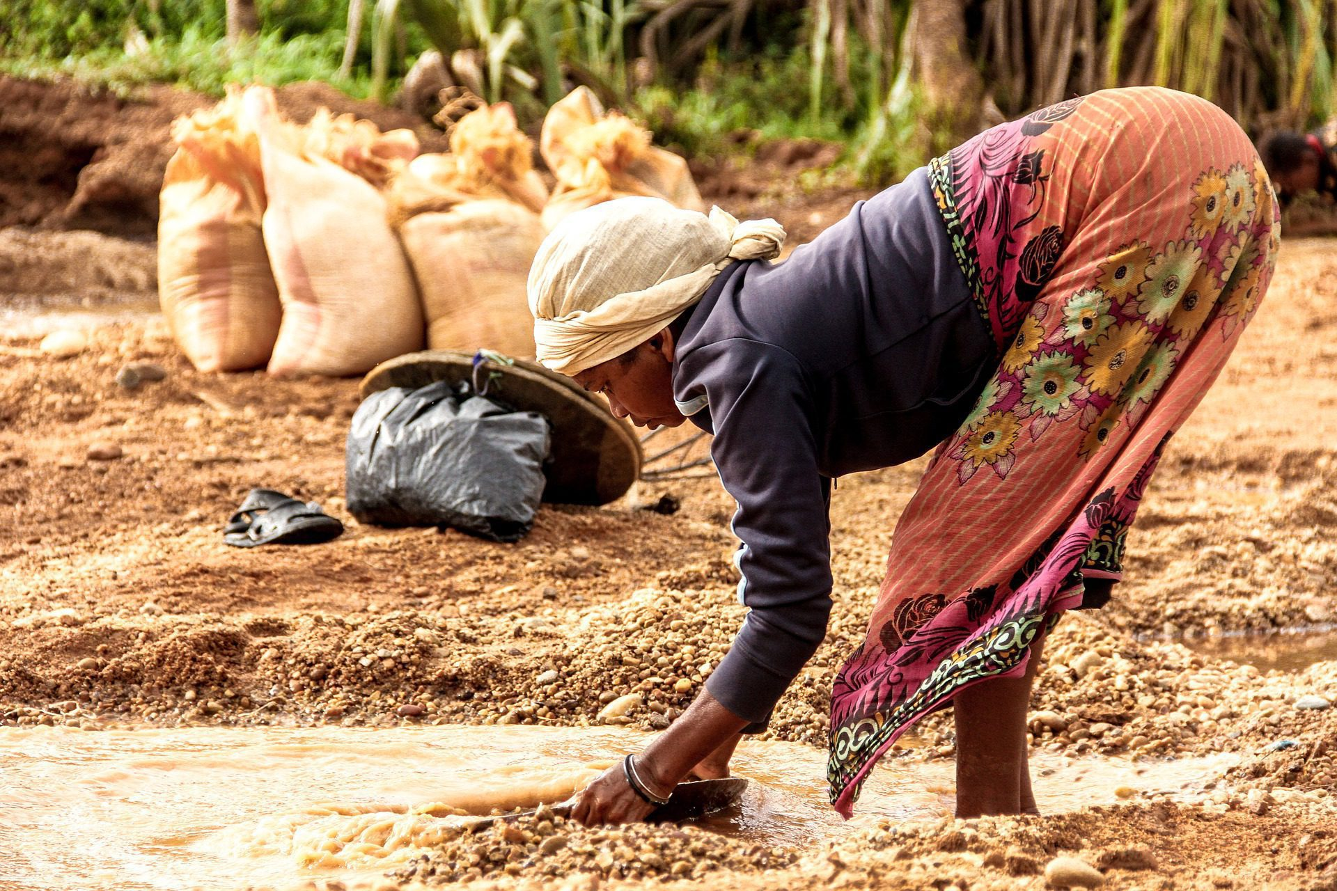 woman tending the soil with bags of grains in Madagascar