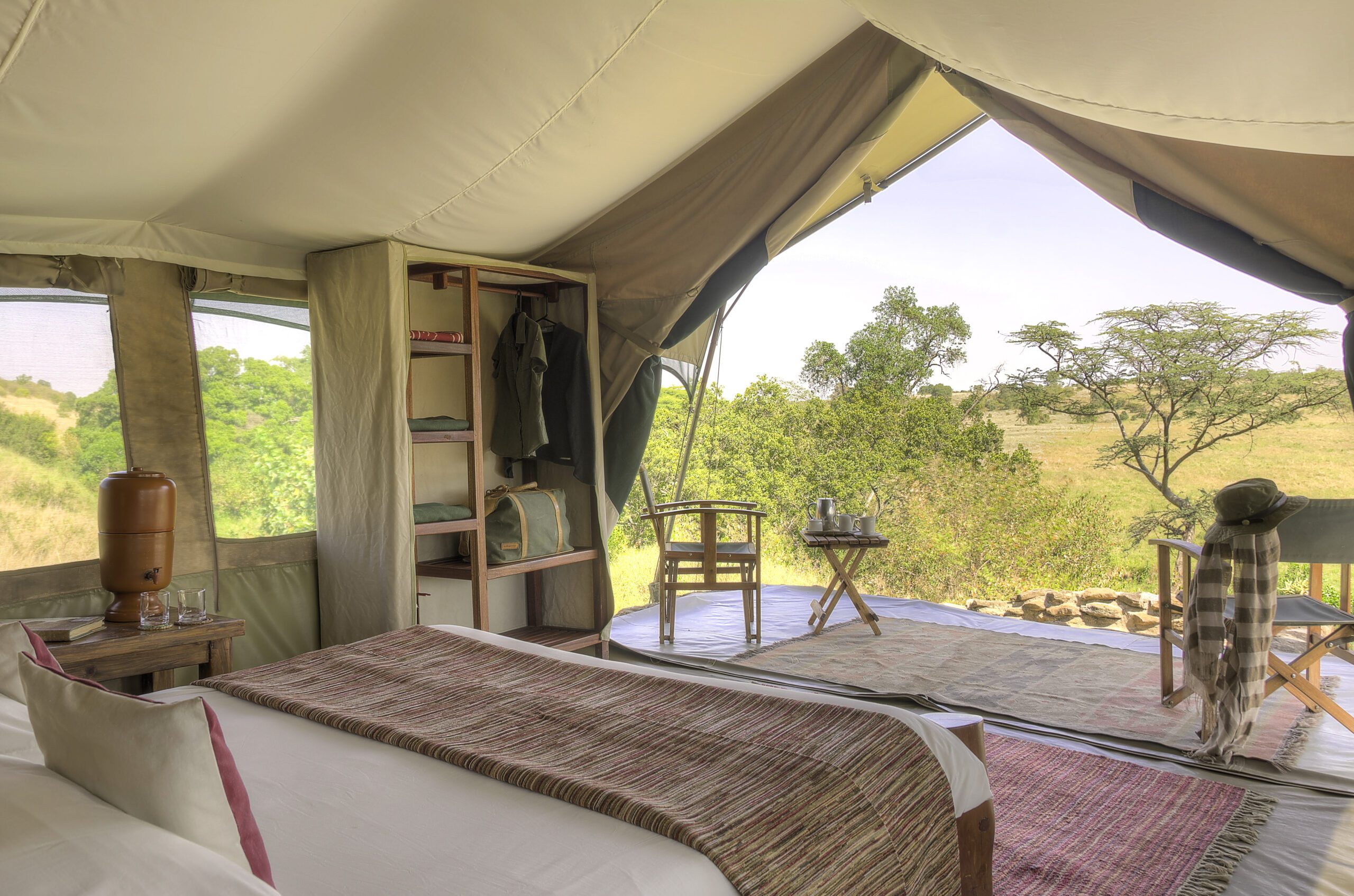 interior view of a tent at Kicheche Mara with a bed, vanity, and chairs overlooking the bush