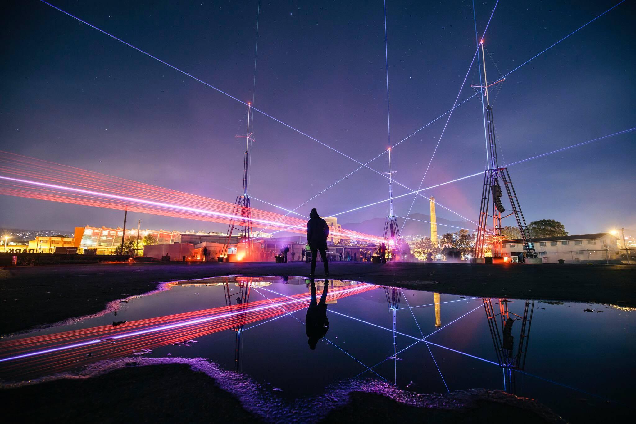 laser lights illuminate the purple night sky at Dark MOFO in Tasmania