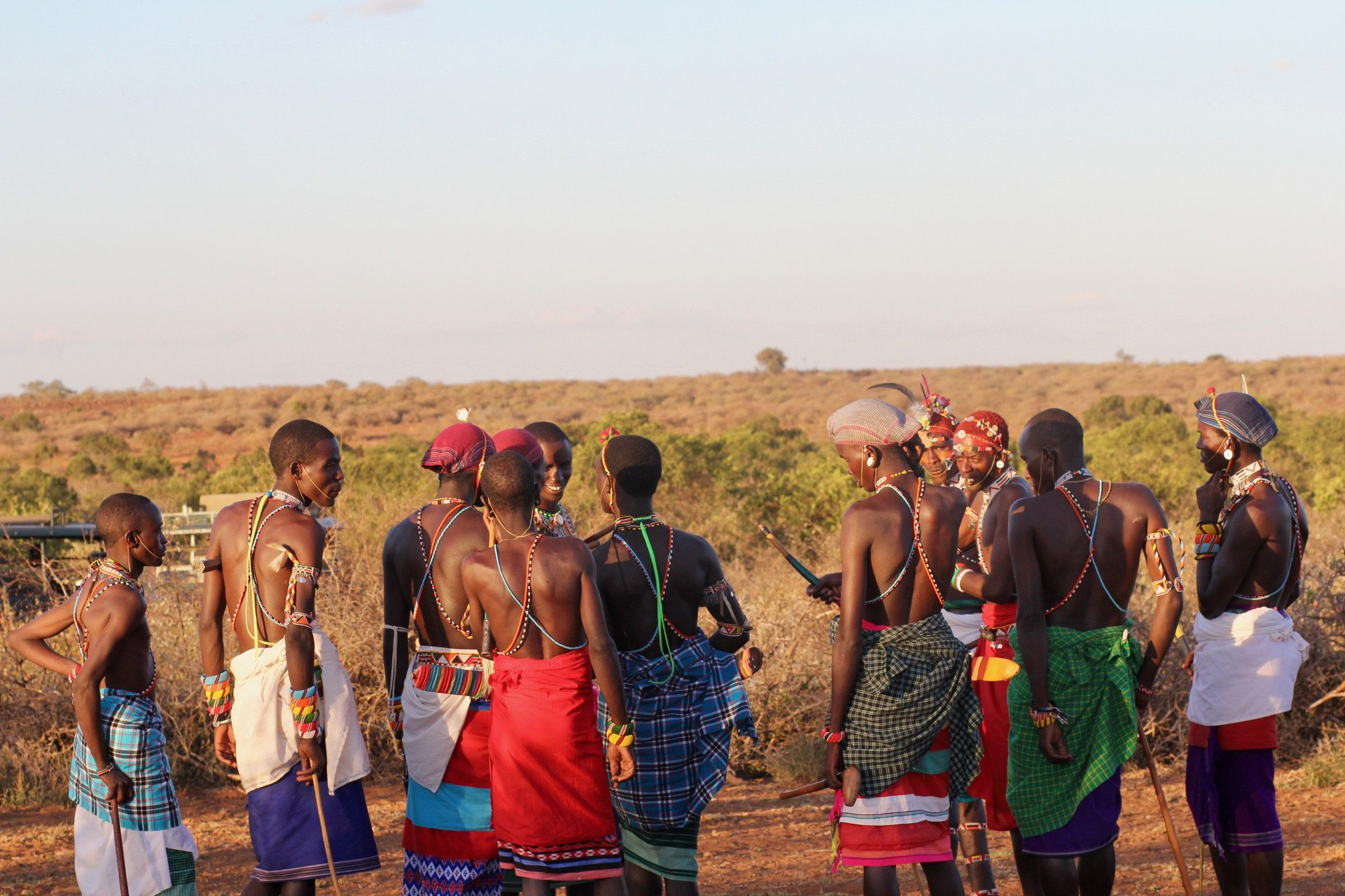 a crowd of Samburu men look out into the landscape while talking among themselves