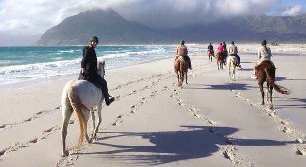 safari on horseback along the white sand beaches in South Africa towards the mountains