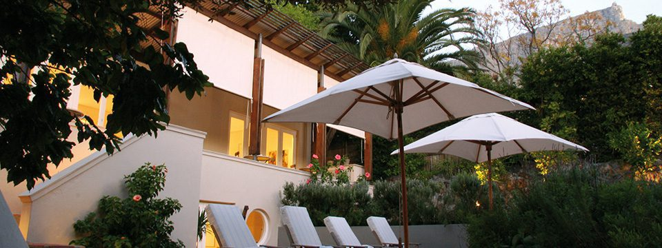 pool chairs and umbrella in front of a hotel and garden in Cape Town on Southern Africa romantic safari
