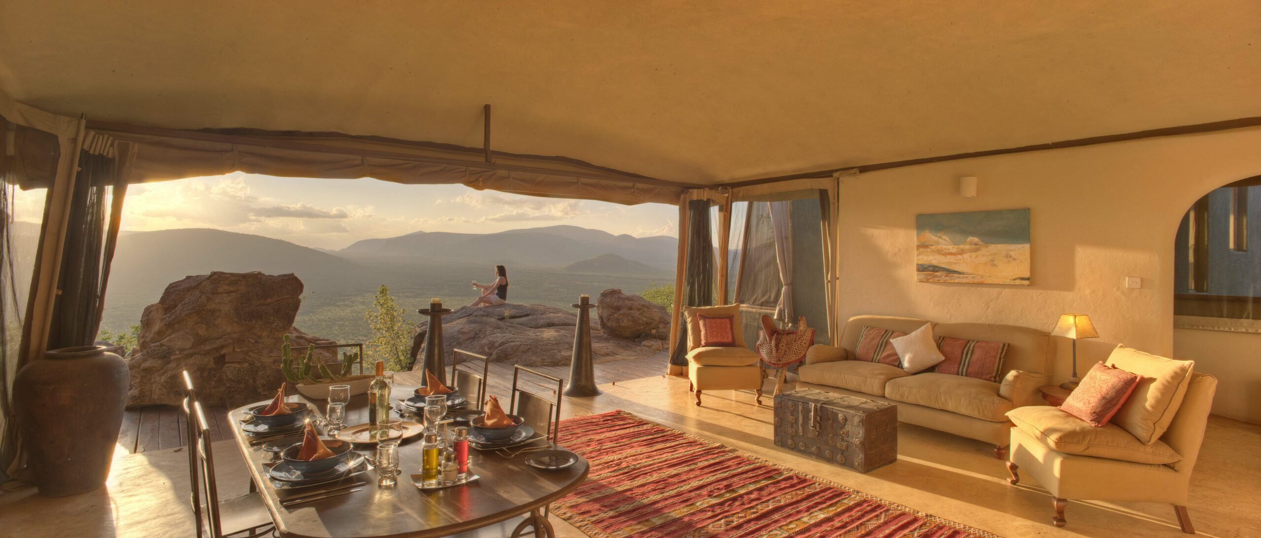 Samburu Saruni's Beautifully decorated room with red rug and open side with views of of a rugged landscape