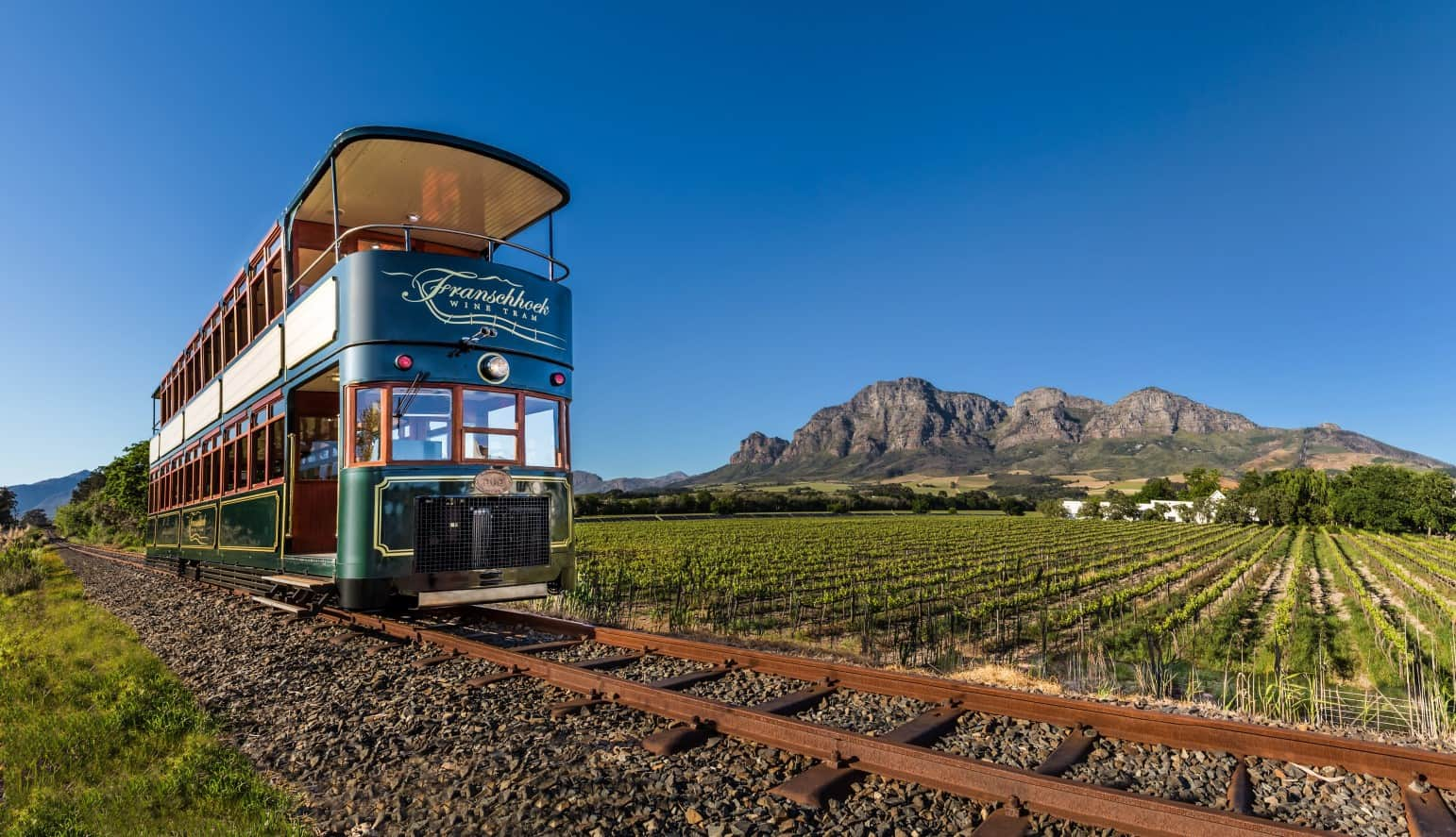 tram on railroad tracks going past vineyards and mountains on a clear day on a Africa food and wine safari