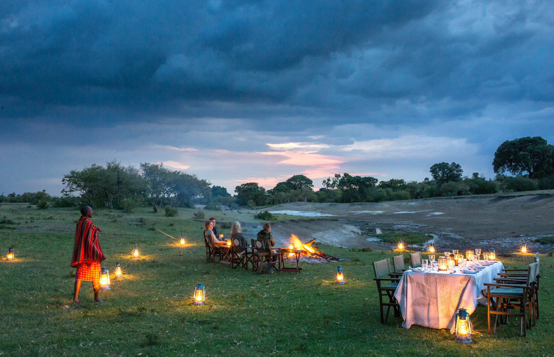 Kenya safari evening dinner on the grass at richard's river camp overlooking the river with candles